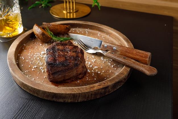 Filet mignon średnio wysmażony podany na drewnianym talerzu z pieczonymi ziemniakami