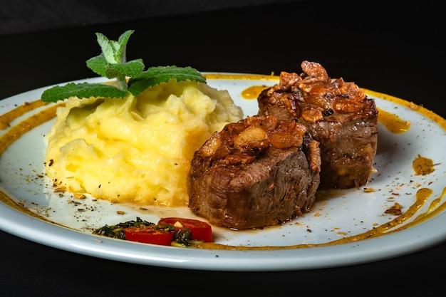 Filet mignon ze smażoną cebulą i puree ziemniaczanym, udekorowany pomidorkami cherry i sosem musztardowym na czarnym tle.