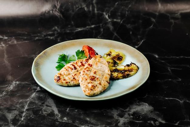 Filet rybny grillowany z bakłażanem i podawany z pomidorami i natką pietruszki.