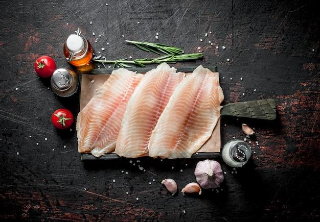 Filet rybny na desce do krojenia z rozmarynem, czosnkiem i przyprawami.