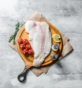 Filet rybny na desce do krojenia z rozmarynem, pomidorami, plasterkami cytryny i przyprawami.