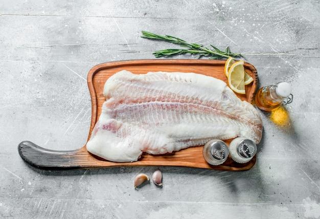 Filet rybny na desce do krojenia z rozmarynem, przyprawami, plasterkami cytryny i oliwą.