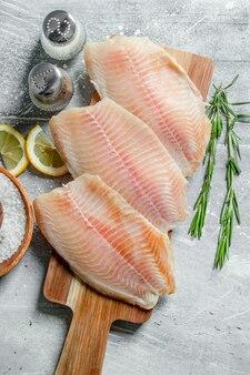 Filet rybny na drewnianej desce do krojenia z rozmarynem, przyprawami i plasterkami cytryny.
