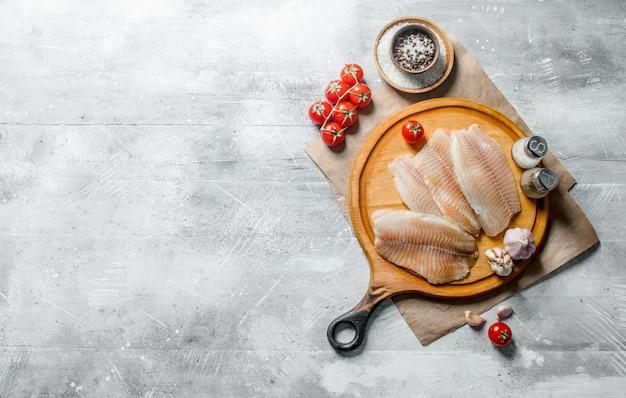 Filet rybny na okrągłej desce do krojenia z przyprawami, pomidorami i czosnkiem.