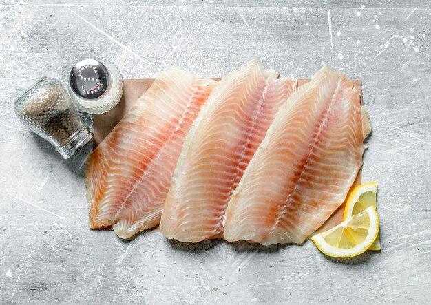 Filet rybny na papierze z przyprawami i kawałkami cytryny.