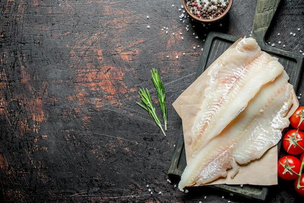 Filet rybny na papierze z rozmarynem, pomidorami na gałęzi i przyprawami w misce. na ciemnym tle rustykalnym