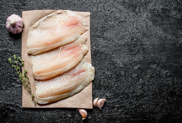 Filet rybny na papierze z tymiankiem i ząbkami czosnku.