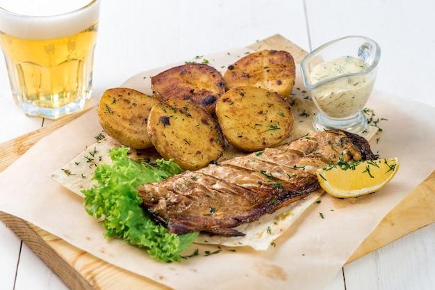 Filet rybny smażone ziemniaki z zieloną cytryną i sosem na drewnianej desce