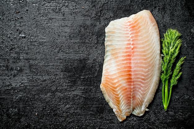 Filet rybny z koperkiem. na czarnym tle rustykalnym