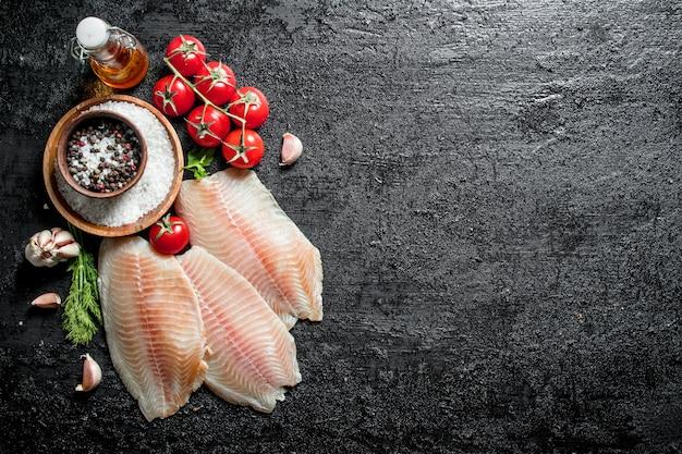 Filet rybny z pomidorami na gałęzi, przyprawami i olejem w butelce.