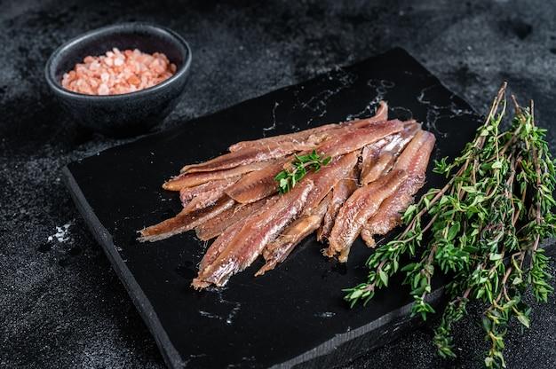 Filet rybny z sardeli w oliwie z oliwek. czarne tło. widok z góry.