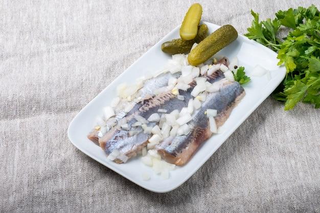 Filet śledziowy z cebulą na białym talerzu i szarym tle z teksturą.