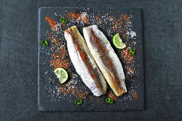 Filet śledziowy z solą morską i przyprawami na kamiennej czarnej desce. filety ze śledzia norweskiego