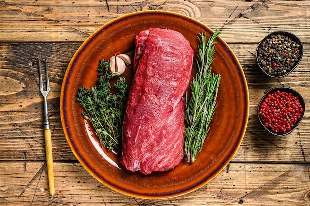 Filet w całości surowy mięso cielęce z polędwicy wołowej na steki. drewniane tła. widok z góry.