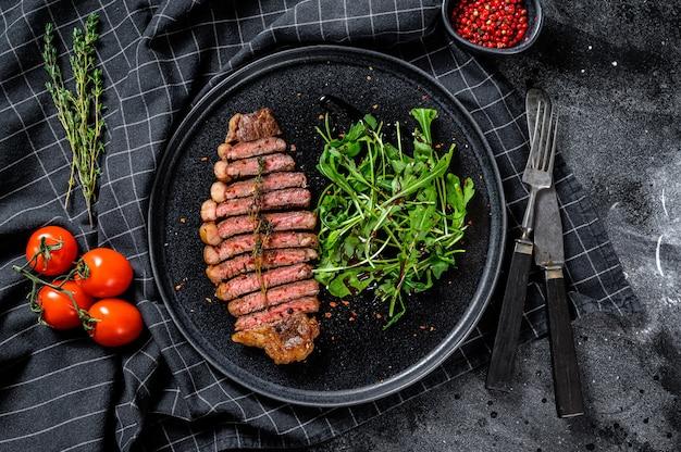 Filet z antrykotu, marmurkowe mięso wołowe z rukolą. czarne tło. widok z góry