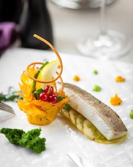 Filet z białej ryby na plasterkach cytryny i sałatka z frytkami.