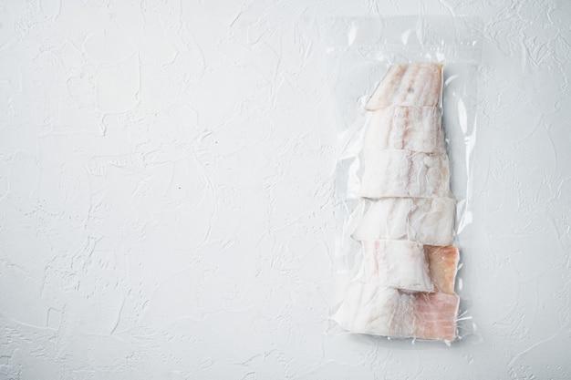 Filet z białej ryby z plamiaka w plastikowym opakowaniu, na białym stole, widok z góry