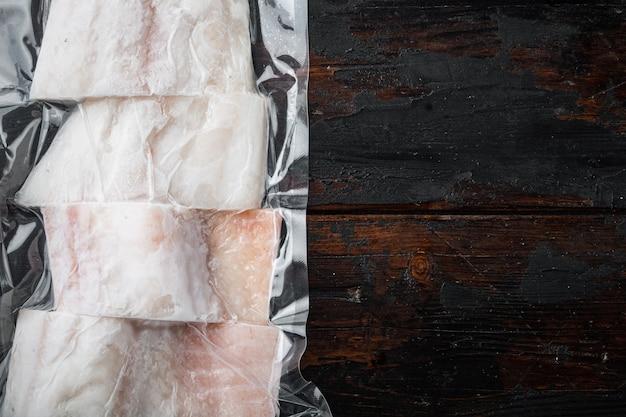 Filet z białej ryby z plamiaka w plastikowym opakowaniu, na ciemnym drewnianym stole, widok z góry