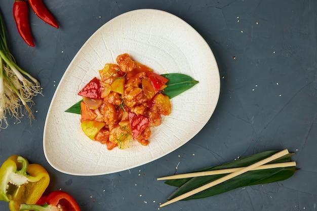 Filet z kurczaka w sosie słodko-kwaśnym, kuchnia chińska, tło betonowe