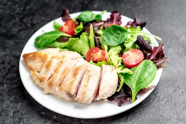Filet z kurczaka z sałatką i szpinakiem zdrowa żywność na kamiennym stole