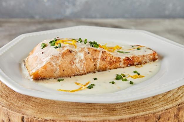 Filet z łososia w sosie beszamelowym ze skórką pomarańczową i zieloną cebulką. kuchnia francuska jedzenie dla smakoszy.