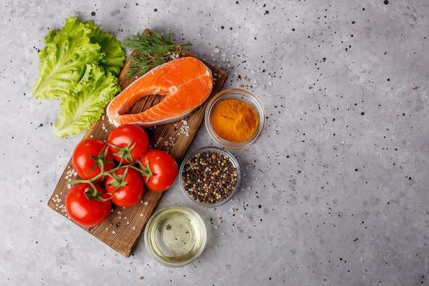 Filet z łososia z przyprawami i warzywami na szarej przestrzeni. edukacja kulinarna. miejsce na żywność. bilans zdrowej żywności. menu obszaru tabel. kopia przestrzeni.