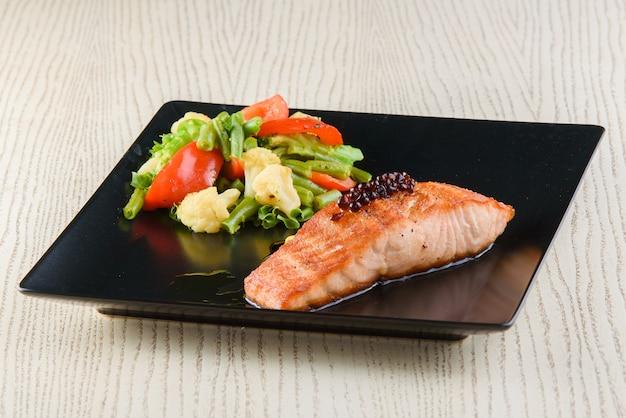 Filet z łososia ze smażonymi warzywami na kwadratowych czarnych talerzach na białym drewnianym stole.