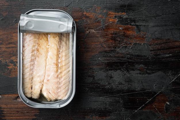 Filet z makreli w puszce, przetwory rybne, w puszce, na starym ciemnym drewnianym stole