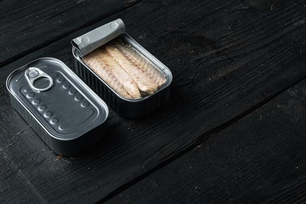 Filet z makreli w puszce, zestaw przetworów rybnych, w puszce, na czarnym drewnianym stole