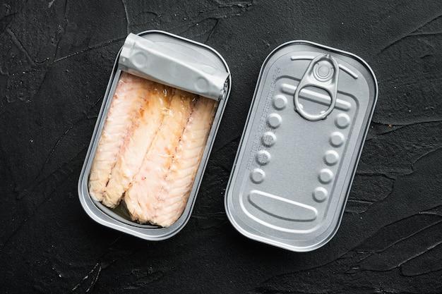 Filet z makreli w puszkach, zestaw konserw rybnych, w puszce, na czarnym stole, widok z góry na płasko