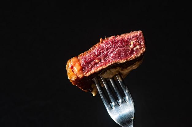 Filet z mignon na szpikulcu na widelcu, ukazujący czubek mięsa z grilla na czarnym tle. rzadkie mięso.