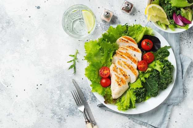 Filet z piersi kurczaka i sałatka warzywna z pomidorami i zielonymi liśćmi. pojęcie zdrowej żywności i diety ketonowej. widok z góry.