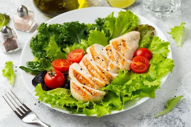 Filet z piersi kurczaka i sałatka warzywna z pomidorami i zielonymi liśćmi. pojęcie zdrowej żywności i diety ketonowej.