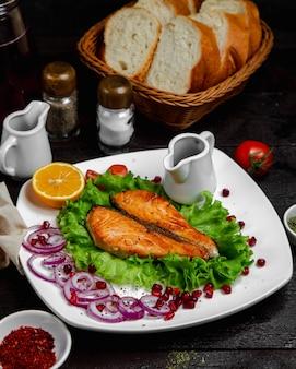 Filet z ryby faszerowany i podany w liściu sałaty z cebulą i cytryną.