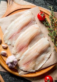 Filet z ryby tilapia na desce do krojenia z ząbkami czosnku, pomidorami i tymiankiem.