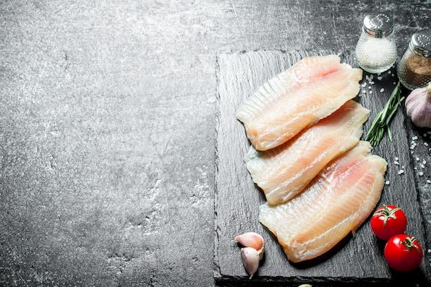Filet z ryby tilapia na kamiennym talerzu z pomidorami, ząbkami czosnku i przyprawami.