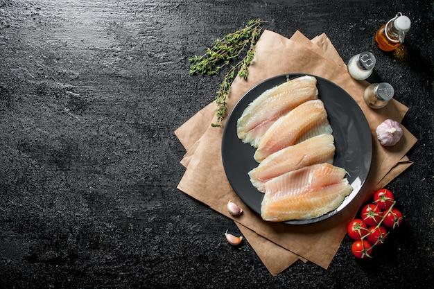 Filet z ryby tilapia na talerzu z papierem, przyprawami, tymiankiem i pomidorami.