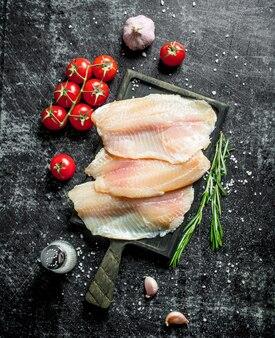 Filet z ryby tilapia z pomidorami na gałęzi, rozmarynem, czosnkiem i solą.