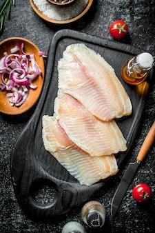 Filet z ryby tilapia z przyprawami i cebulą w miseczkach.