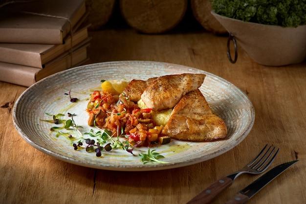 Filet z sandacza i tłuczone ziemniaki, danie na talerzu na drewnianym stole.