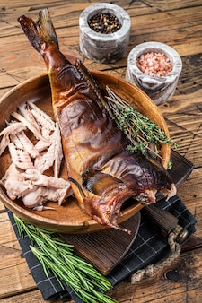 Filet z sandacza lub sandacza wędzonego na gorąco w drewnianym talerzu z ziołami. drewniane tła. widok z góry.
