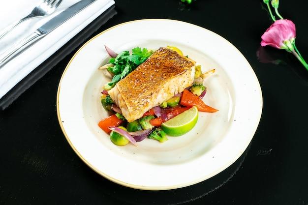 Filet z sandacza w pikantnym słodkim sosie na poduszce z gotowanych warzyw w żółtym talerzu na ciemno. smaczne i zdrowe jedzenie. obsługa restauracji zdjęcie żywności według przepisu lub menu
