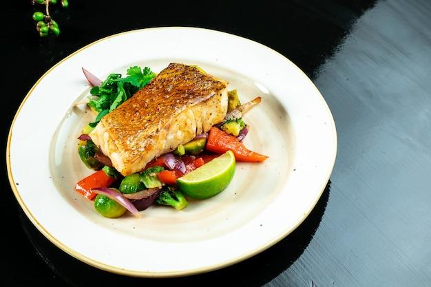 Filet z sandacza w pikantnym słodkim sosie na poduszce z gotowanych warzyw w żółtym talerzu na ciemnym tle.