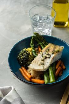 Filet z sandacza ze szparagami, brokułami i marchewką. smażona ryba z duszonymi zieleniami