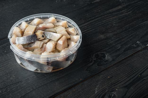 Filet z solonego śledzia holenderskiego w oleju, na czarnym tle drewnianego stołu z kopią miejsca na tekst