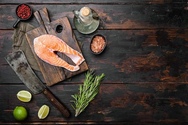Filet z surowego łososia z zestawem świeżych ziół, na starym ciemnym drewnianym stole tło, widok z góry płasko leżał, z miejscem na kopię