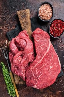 Filet z surowego mięsa wołowego pokrojony na drewnianą deskę do krojenia. ciemne tło. widok z góry.