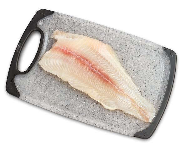 Filet z surowej ryby panga na desce do krojenia. widok z góry. na białym tle.