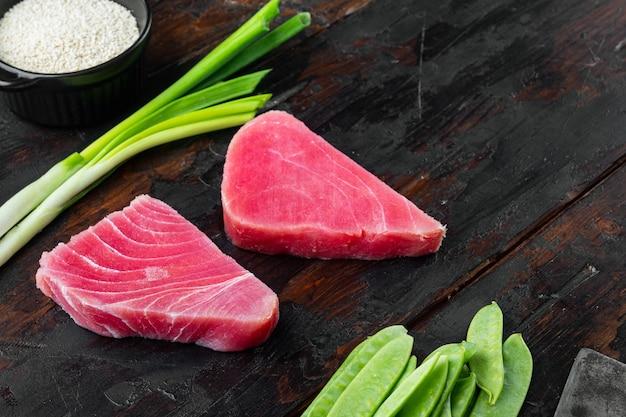 Filet z tuńczyka z surowego ekologicznego steku z zestawem składników, na starym ciemnym drewnianym stole