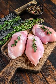 Filet z uda surowego kurczaka bez skóry na drewnianej desce do krojenia. czarne tło. widok z góry.